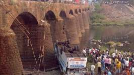 Rescuers and bystanders look at the wreckage of a passenger bus after it fell from a bridge in Ratnagiri district