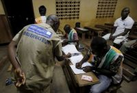 Election observer stands near polling workers as they count the ballots at a polling station in  Yamoussoukro, Ivory Coast